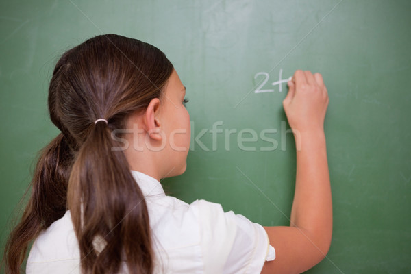 Schoolgirl writing an addition on a blackboard Stock photo © wavebreak_media