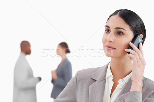 Mobieltje collega's achter witte vrouw telefoon Stockfoto © wavebreak_media