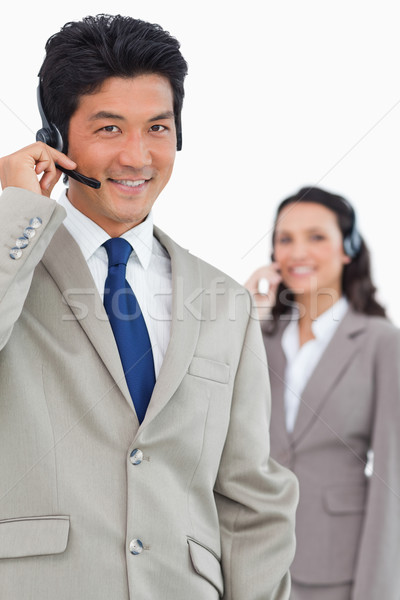 Smiling customer support employee with colleague behind him against a white background Stock photo © wavebreak_media