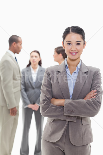 Businesswoman smiling and crossing her arms with co-workers talking in the background Stock photo © wavebreak_media
