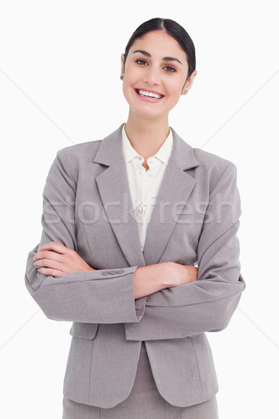 Smiling young saleswoman with arms crossed against a white background Stock photo © wavebreak_media