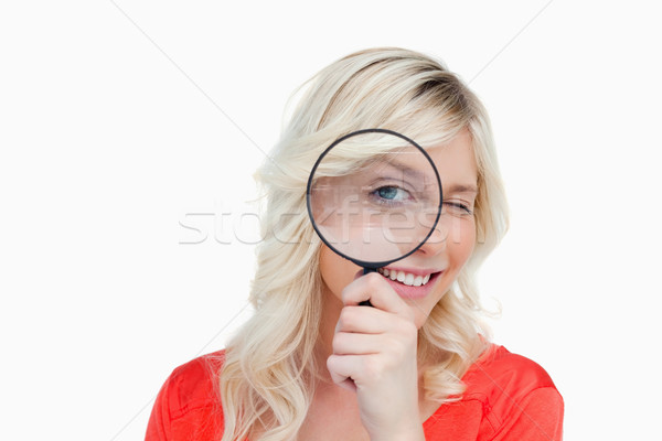 Woman looking through a magnifying glass while showing a blink of an eye Stock photo © wavebreak_media