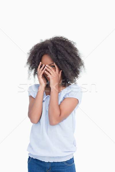 Young woman hiding her face behind her hands against a white background Stock photo © wavebreak_media