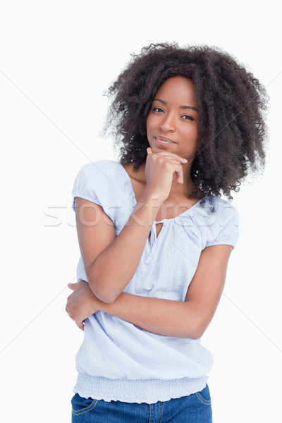Woman standing up with hand on chin and arms crossed against a white background Stock photo © wavebreak_media