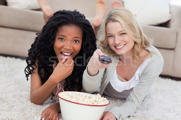 Two women lying on the ground with a bowl of popcorn and a TV romote Stock photo © wavebreak_media