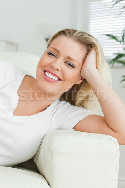 Woman lying on a sofa with a hand in her hair in a living room Stock photo © wavebreak_media
