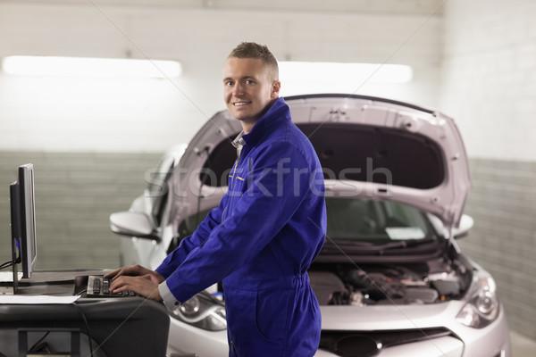 Uśmiechnięty mechanik wpisując komputera garaż szczęśliwy Zdjęcia stock © wavebreak_media