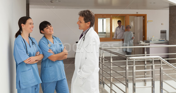 Doctor and two nurses, standing in the hall of a hospital while talking and having fun Stock photo © wavebreak_media