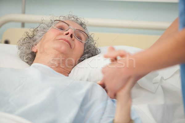 Nurse caring about old woman lying in bed Stock photo © wavebreak_media