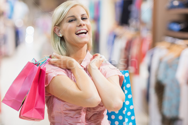 Woman holding two bags laughing in clothes shop Stock photo © wavebreak_media