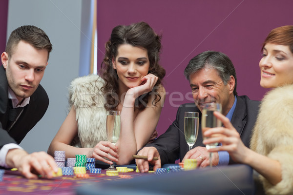 People sitting at the table looking while man placing a bet Stock photo © wavebreak_media