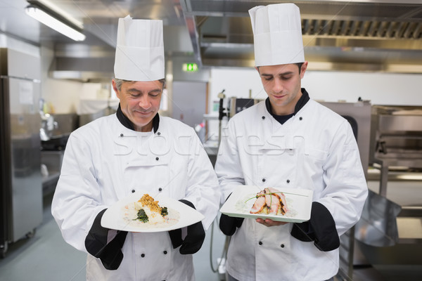 Two Chef's looking down at their dishes in the kitchen Stock photo © wavebreak_media