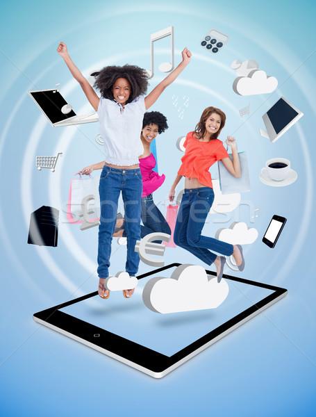 Three cute women jumping on a tablet pc Stock photo © wavebreak_media
