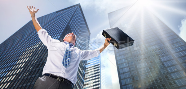 Stock photo: Composite image of businessman holding briefcase and cheering