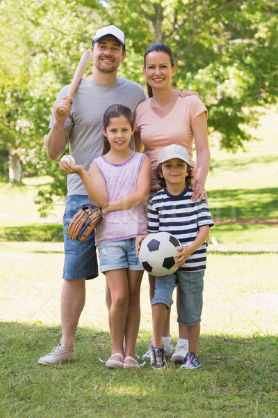 Family of four holding baseball bat and ball in park Stock photo © wavebreak_media
