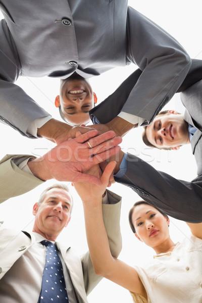 üzleti csapat mosolyog lefelé kamera kezek együtt Stock fotó © wavebreak_media