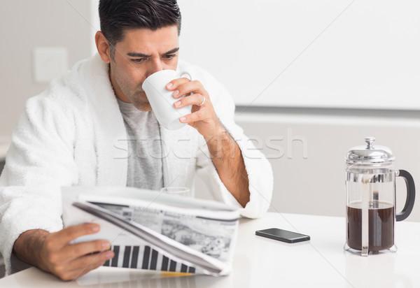 Homem potável café leitura jornal cozinha Foto stock © wavebreak_media
