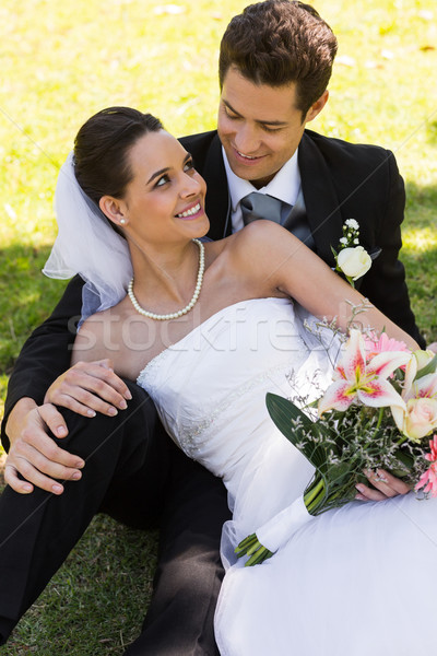 Happy newlywed couple sitting in park Stock photo © wavebreak_media