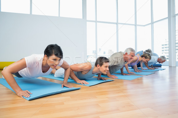 Group doing push ups in row at yoga class Stock photo © wavebreak_media