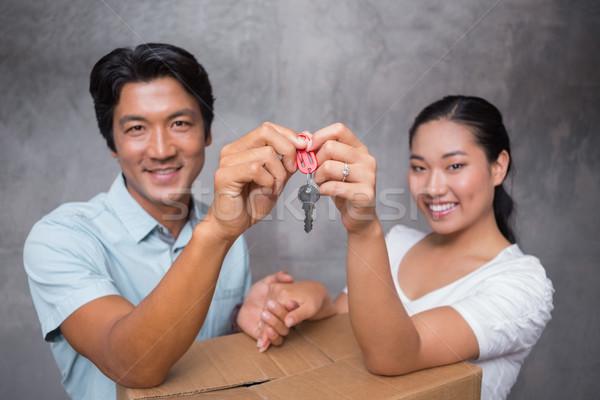 Happy couple holding house key and leaning on moving box Stock photo © wavebreak_media