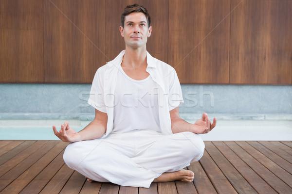Handsome man in white meditating in lotus pose Stock photo © wavebreak_media