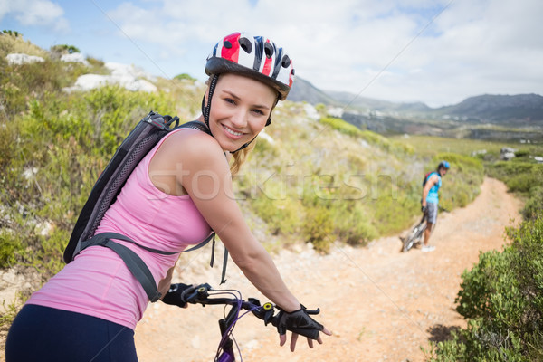 Stock photo: Fit couple cycling on mountain trail woman smiling at camera