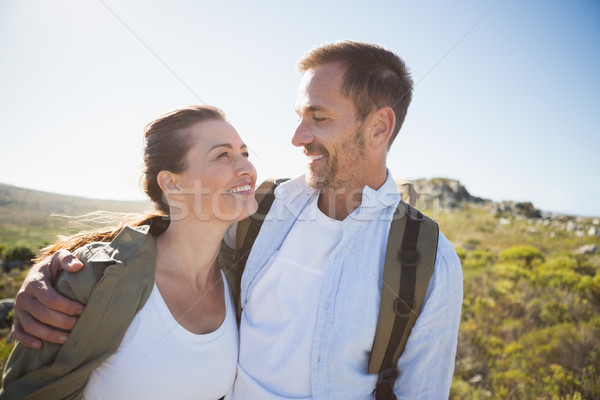 Hiking couple embracing and smiling on country terrain Stock photo © wavebreak_media