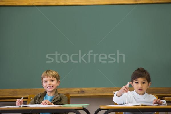 Happy pupils writing in notepad at desks Stock photo © wavebreak_media