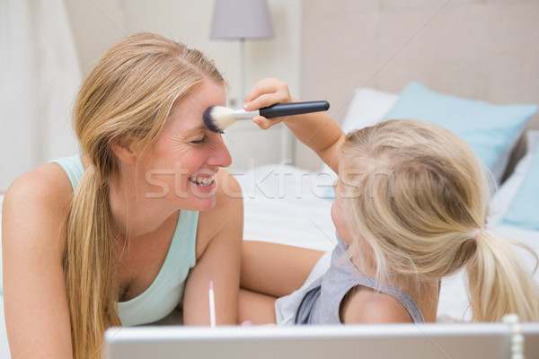 Cute little girl and mother on bed using laptop Stock photo © wavebreak_media