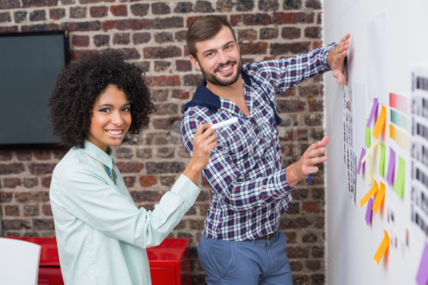 Stock photo: Business team with sticky notes on wall
