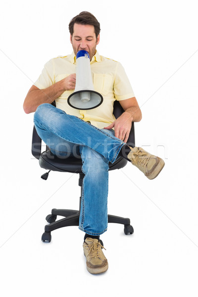 Man sitting on chair shouting through megaphone Stock photo © wavebreak_media