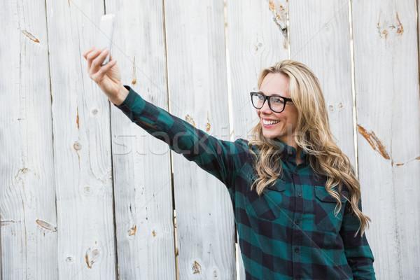 Smiling blonde with glasses taking a selfie Stock photo © wavebreak_media