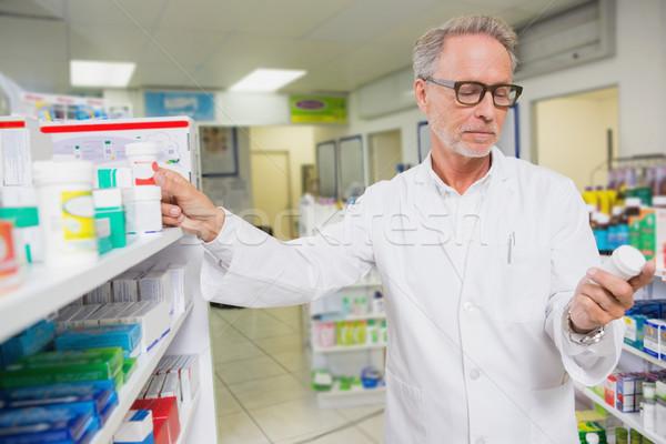 Koncentrált gyógyszerész néz gyógyszer gyógyszertár férfi Stock fotó © wavebreak_media