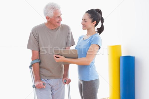 Senior man and his coach looking at clipboard Stock photo © wavebreak_media