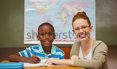 Teacher assisting little boy with homework in classroom Stock photo © wavebreak_media