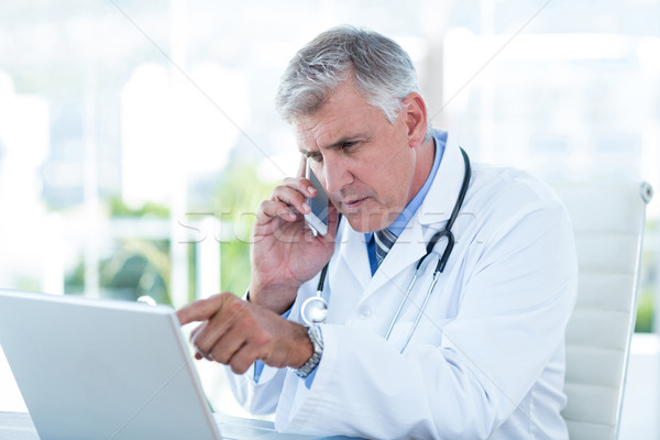 Serious doctor working on laptop and having phone call Stock photo © wavebreak_media