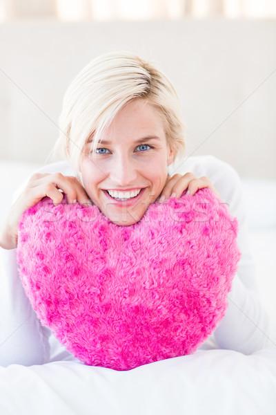 Sorridere donna bionda cuore cuscino camera da letto Foto d'archivio © wavebreak_media