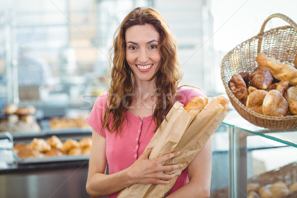 Smiling young brunette with baguettes Stock photo © wavebreak_media