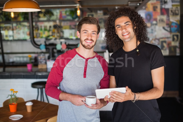 Portrait of smiling young friends using digital tablet in restaurant Stock photo © wavebreak_media
