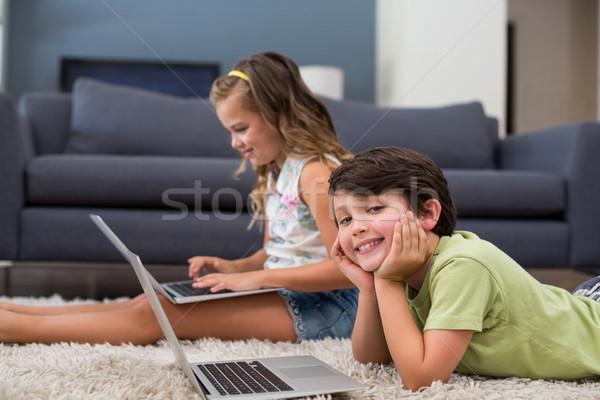 Stock photo: Siblings using laptop in living room