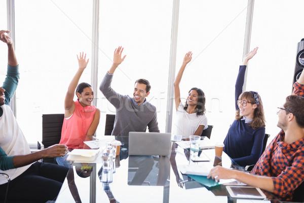 Boldog üzletemberek karok a magasban ül asztal iroda Stock fotó © wavebreak_media