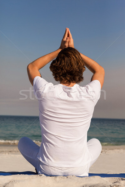 Man performing yoga at beach Stock photo © wavebreak_media