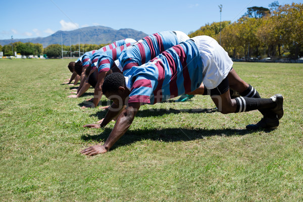 Side view of rugby players exercising at grassy field Stock photo © wavebreak_media