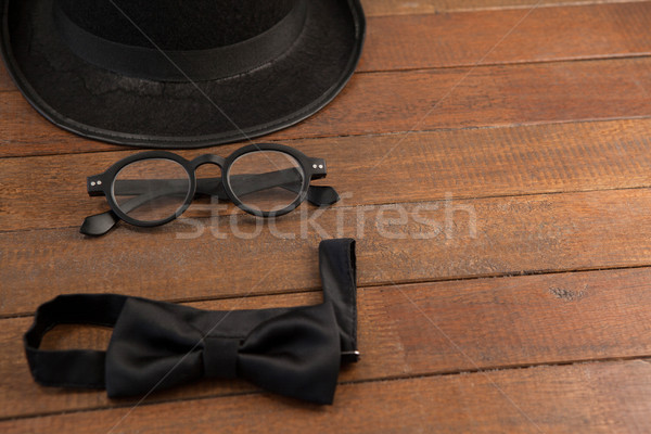 Hat, spectacles and bow tie arranged on wooden background Stock photo © wavebreak_media
