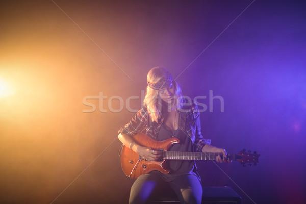 Female guitarist performing in illuminated nightclub Stock photo © wavebreak_media