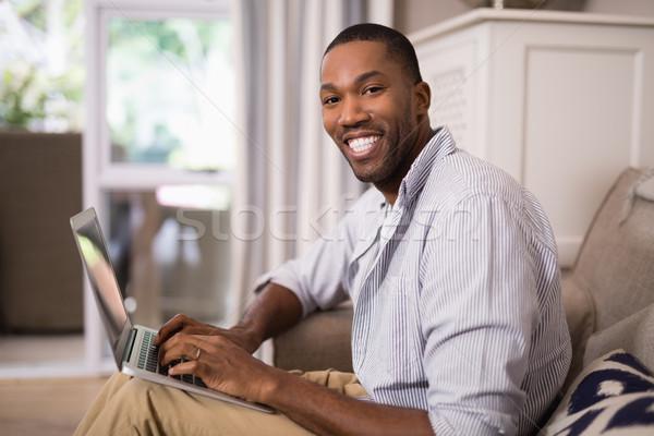 Smiling young man using laptop at home Stock photo © wavebreak_media