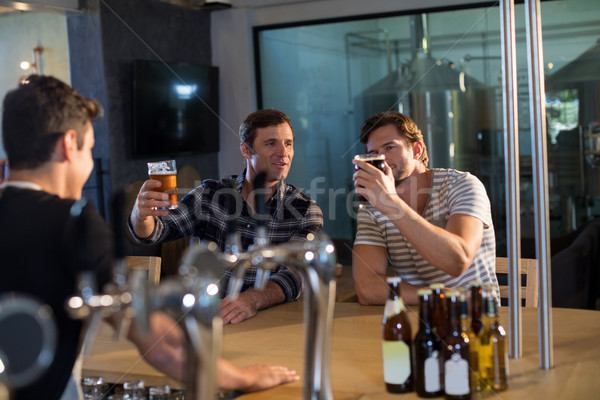Barátok élvezi sör bár fehér ül Stock fotó © wavebreak_media