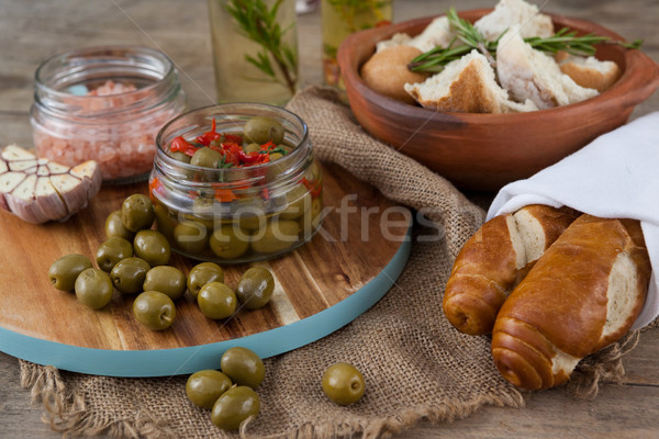 Green olives with containers on cutting board by bread Stock photo © wavebreak_media