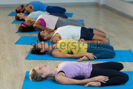 Smiling trainer exercising while lying down with senior people Stock photo © wavebreak_media