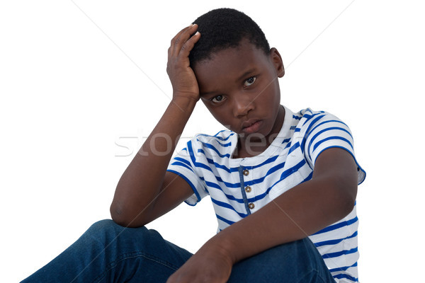 Stock photo: Sad boy sitting with hand on head against white background